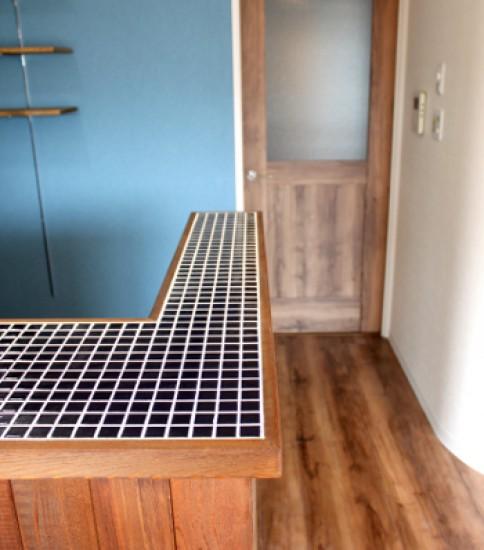ブルーの壁とウッドでコーディネートしたマンションのキッチン